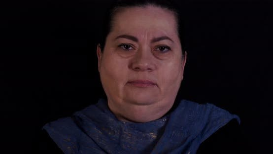Elder woman looks at the camera with glazed eyes