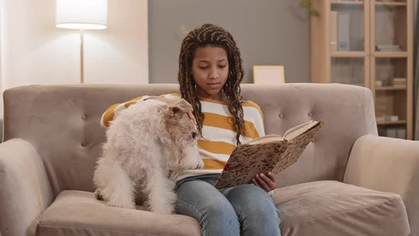 Girl Reading Sitting with Dog