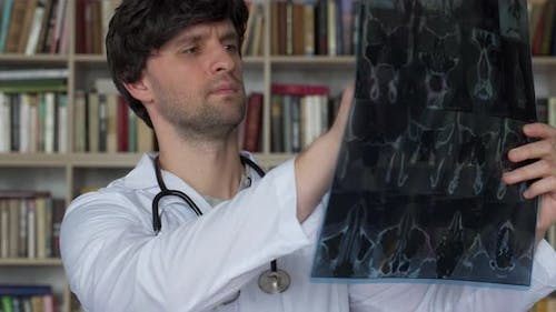 Man Doctor Looks at an Xray of a Patient in the Clinic
