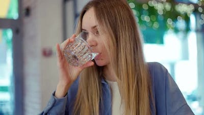 Young Woman Drinking Water in a Cafe