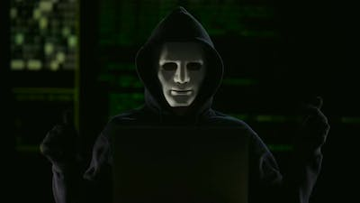 Hacker in mask and gloves breaking government servers