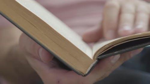 Gros plan des mains masculines feuilletant les pages du livre à l'intérieur. Concept de Connaissances