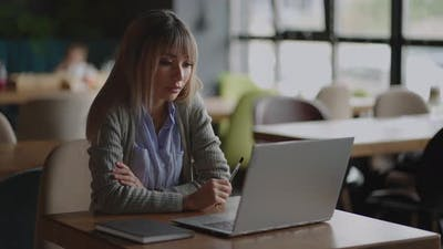 An Asian Woman Sits Brooding and Looks at a Laptop Screen