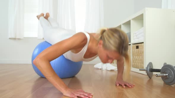 Thumbnail for Healthy blonde woman doing push ups with balance ball
