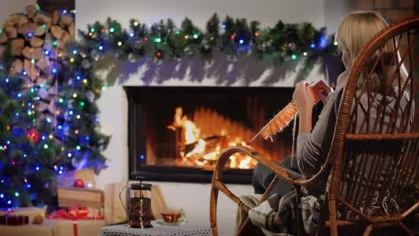 Thumbnail for Rückansicht einer Frau strickt beim Sitzen durch einen Kamin Dekoriert für Weihnachten