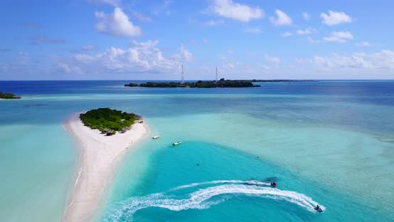 Daytime overhead copy space shot of a sandy white paradise beach and blue water background in colorf