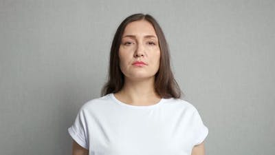 Sad Woman Expresses Refusal Crossing Arms in Grey Studio