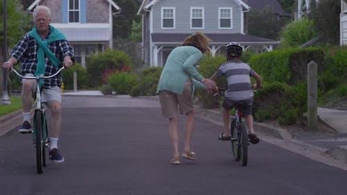 Grandparents riding bikes with grandson