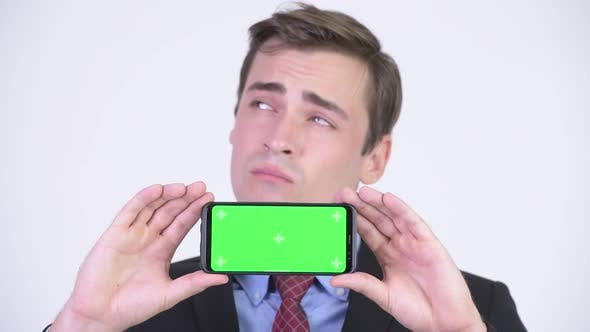 Thumbnail for Young Handsome Businessman Thinking While Showing Phone