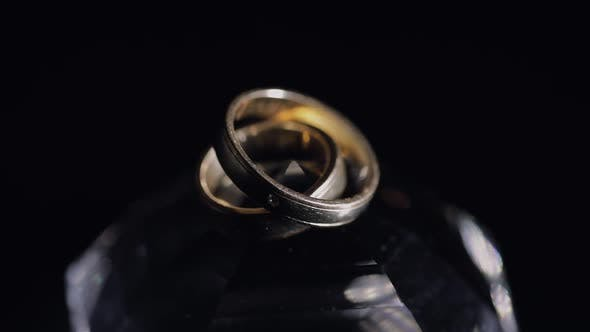 Thumbnail for Wedding Rings Lying on Crystal Shining with Light Close Up Macro