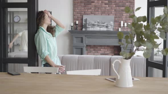 Cover Image for Tired Young Mother Trying To Calm Herself Standing Near the Wall with Glass of Water