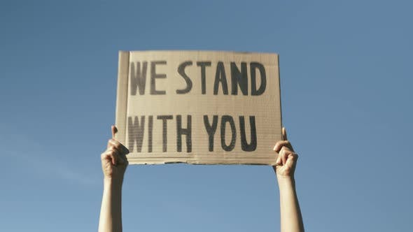 """Thumbnail for Sign WE STAND WITH YOU against blue sky. Woman hands waving poster """"We Stand With You""""."""