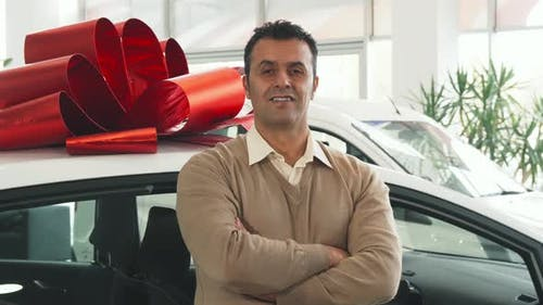 A Solid Man Stands on the Background of a Car with a Gift Bow