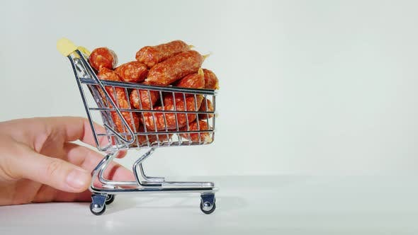 Thumbnail for Hand Rolls Out a Small Shopping Trolley with Sausages.