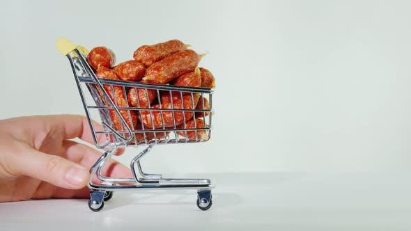 Handrollt einen kleinen Einkaufswagen mit Würstchen aus.