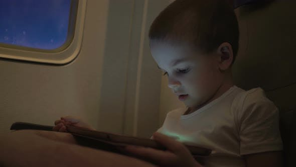 Thumbnail for Cute Boy Traveling in an Airplane and Playing with a Computer Tablet