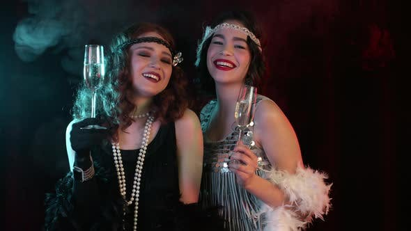 Beautiful Flappers Women Dressed in Style of Roaring Twenties Drinking Champagne. Vintage, Retro