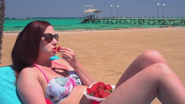 Mädchen isst Erdbeeren am Strand