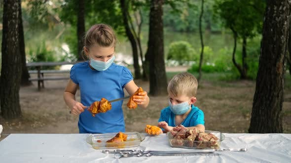 Little boy and girl put marinated meat on a skewer. Children in medical masks