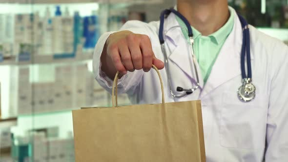 Thumbnail for Doctor Smiling and Holding a Package in Drugstore