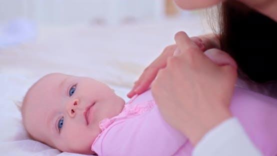 Großes Porträt, eines Babys mit blauen Augen, Mama streichelt mit der Hand, Mamas Liebe und Fürsorge
