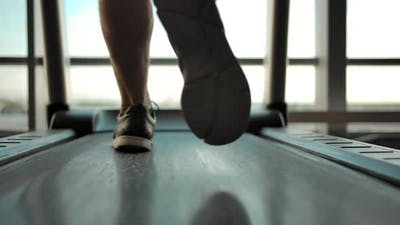Legs of a Male Athlete on a Treadmill