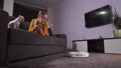 Young Woman Controlling Robot Via Mobile App