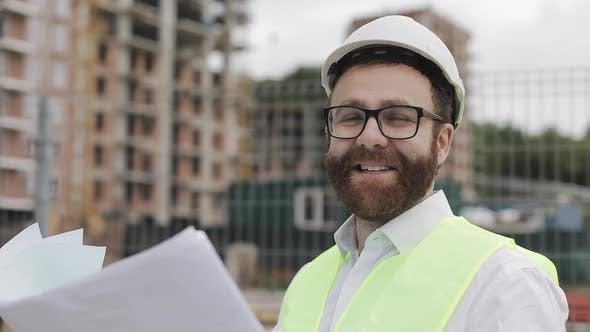 Thumbnail for Portrait of a Successful Young Engineer or Architect Wearing a White Helmet, Holding Construction