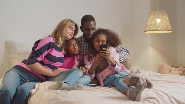 Thumbnail for Interracial Familie mit Mädchen, die Selfie auf dem Bett nehmen