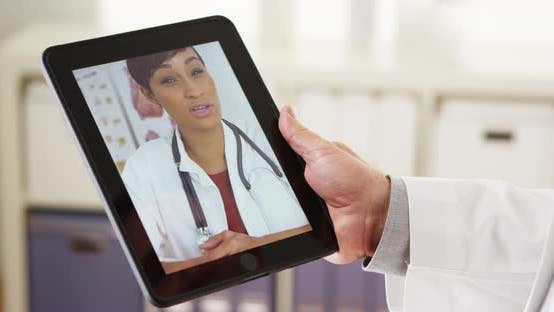 Thumbnail for Doctors video chatting on tablet