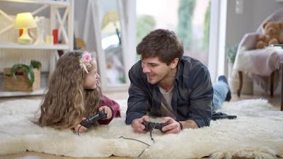 Cheerful Father and Daughter Using Game Consoles Playing Video Game at Home on Weekends