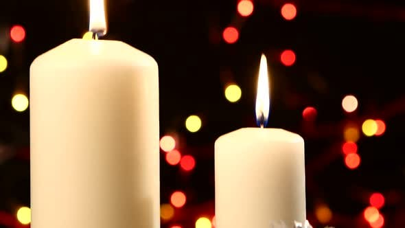 Thumbnail for Two Big White Candles with Christmas Decorations Like Red Bow, Balls and Tree on Black, Bokeh, Light