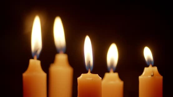 Kerzen werden mit einer hellen Flamme angezündet.