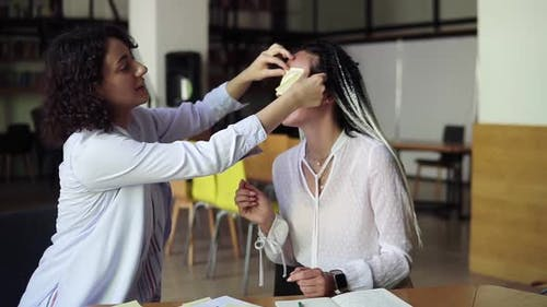Two Caucasian Women Making Fun During Their Preparation for Exams