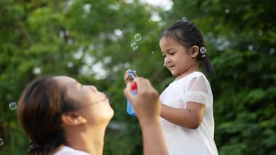 Mom and daughter blowing and catching soap bubbles