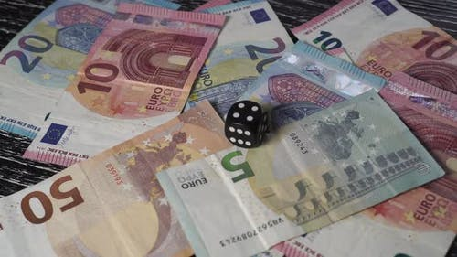 On a pile of euro banknotes, a hand lays a black dice with the number 4 on top.