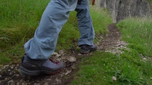 A hiker is hiking on a mountain trail.