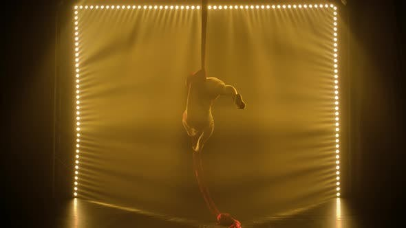 Equilibrium Gymnast Stretched and Rotating on a Red Silk. Silhouette Young Girl Performs the
