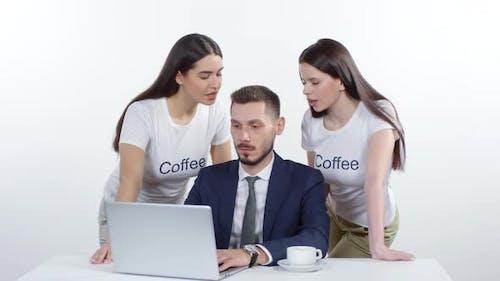 Women Tempting Businessman to Drink Coffee