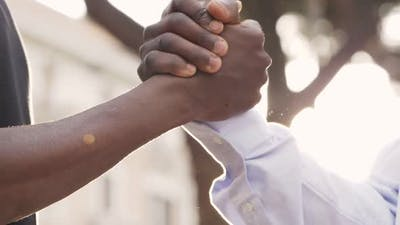 close up on black people greetings. Shaking hands - slow motion