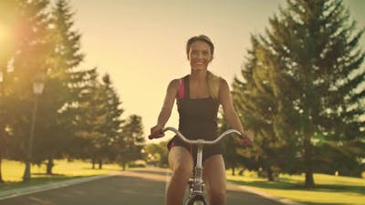 Young Woman Cycling on Bicycle in Summer Park. Happy Woman Riding Bicycle