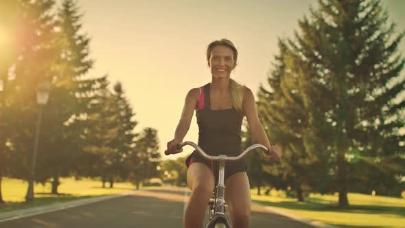 Thumbnail for Young Woman Cycling on Bicycle in Summer Park. Happy Woman Riding Bicycle