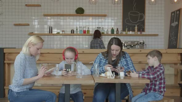 Thumbnail for Women and Kids Using Phones Sitting at Cafe Table