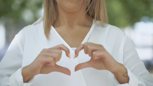Thumbnail for Cropped Shot of Girl Showing Hand Heart