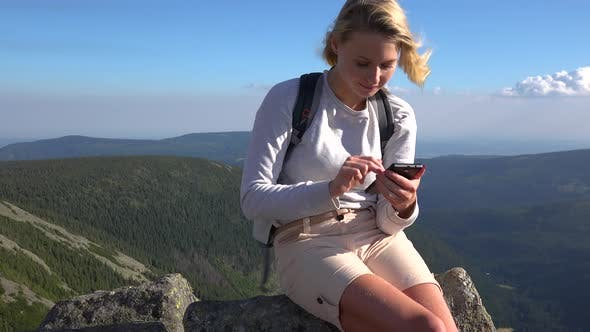 Thumbnail for A Young Beautiful Woman Sits on a Rock on a Hilltop and Works on a Smartphone