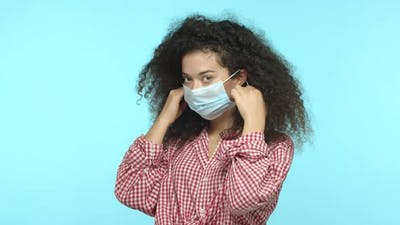 Young Woman Takes Off Medical Mask