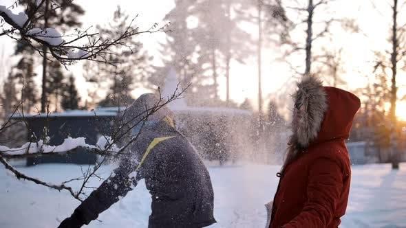 Молодая влюбленная пара бросает снег в воздух