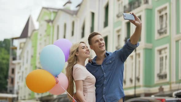 Cover Image for Young Female and Male in Love Hugging and Taking Selfie, Romantic Memories