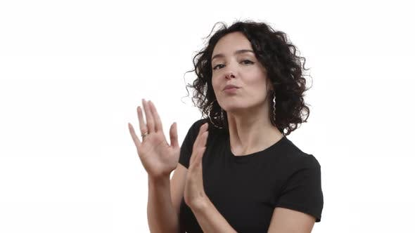 Cheerful Caucasian Woman with Dark Curly Hairstyle Wearing Black Tshirt Dancing From Rejoice and