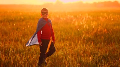 Little Boy Plays and Dreams of a Super Hero at Sunset